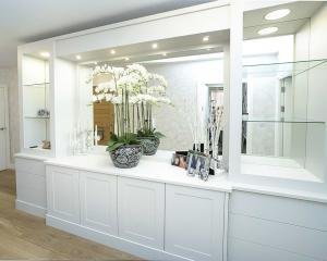 Large built in living room cupboards with mirrored backing and breakfront cupboards
