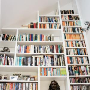 Very tall Contemporary modern Home library with asymeterical shelving