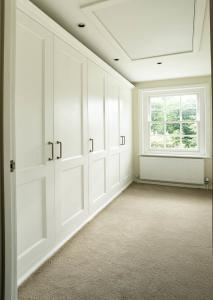 Fitted Victorian wardrobes in a bedroom with D handles