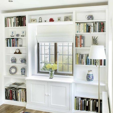 Bespoke fitted bookcases surrounding a break front cabinet