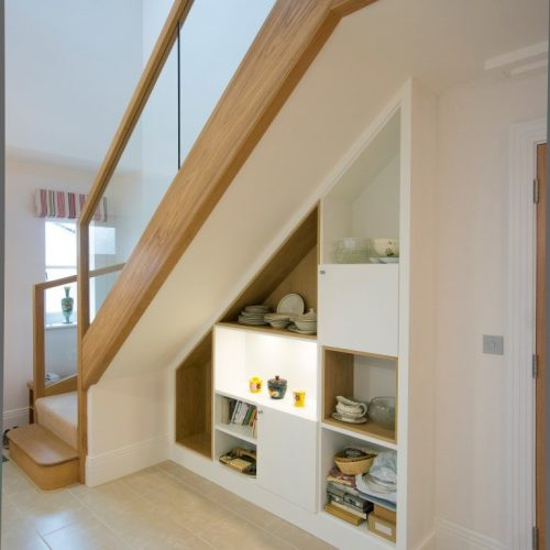 Modern fitted cupboards under stairs with shelving