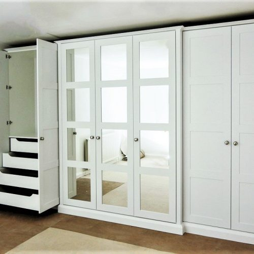 Break front four panel mirrored shaker doors in this wardrobe provide an interesting central feature on this long run of wardrobes. With internal storage with drawers hanging and shelves. Theres plenty of wardrobe space to buy yourself some more clothes!
