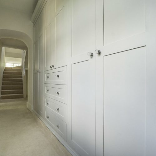 Period Victorian wardrobe fitted to a narrow hallway. Detailed with panelled shaker doors, finished with detailed plinth and cornice detail and fluted pilasters